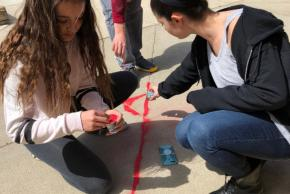 students filling sidewalk cracks with red sand